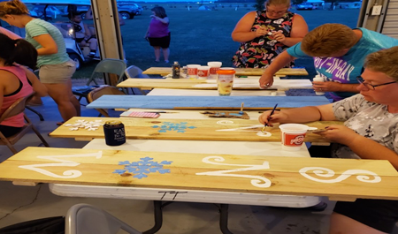painting wooden signs at Tall Timbers
